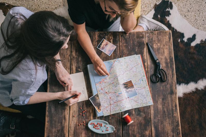Eine Gruppe von Freunden, die sich eine Karte ansehen, bevor sie sich auf den Weg zu einer Wanderung machen